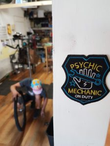 "A mechanic bent over a bike wheel in the fuzzy back ground, a patch statin ""Psychic mechanic at work' focused in the foreground"